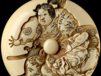Detail of a manju netsuke depicting Minamoto Yoshitsune practising martial arts with a tengu demon,