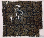 Textile fragment with rosettes or wheel-shapes, flowers, and plants (EA1990.236)