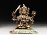 Seated figure of a multi-headed and multi-armed crowned female deity