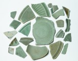 Group of greenware sherds with one blue and white fragment