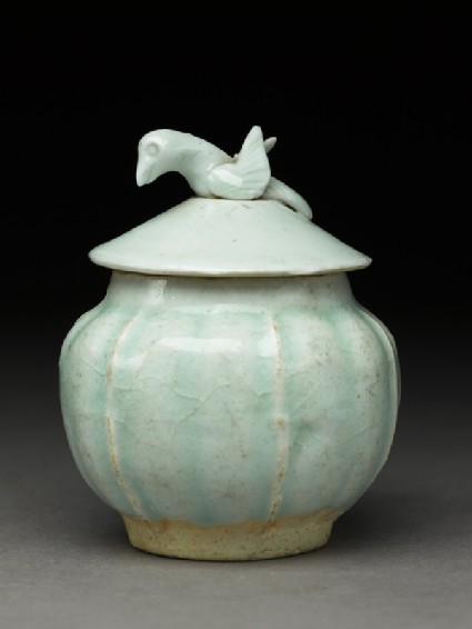 Lidded white ware jar surmounted by birdside