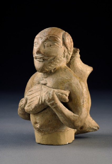 Figure of a musician carrying a water-skinoblique