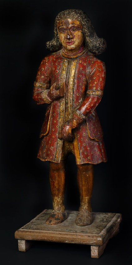 Figure of a standing Dutchman wearing a red coatoblique