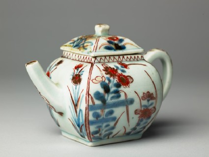 Teapot with two types of flowering plantsside