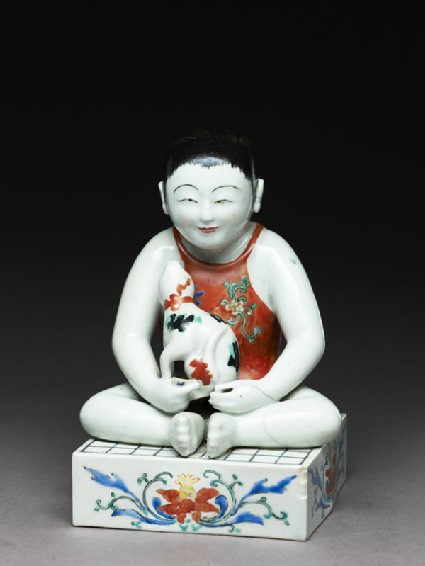 Figure of a boy seated on a shogi, or chess boardside