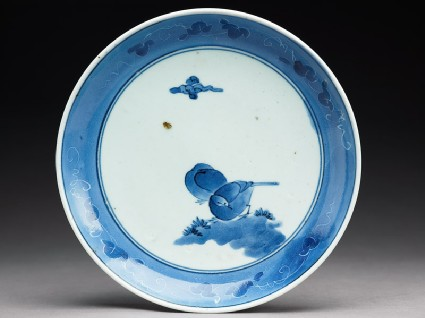 Plate with two birds under a cloudtop