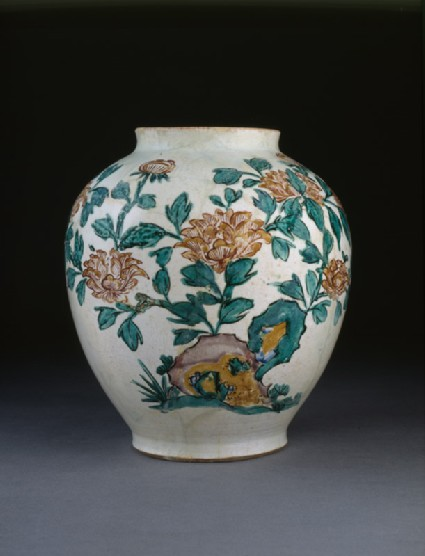 Jar with flowering plants and butterfliesside