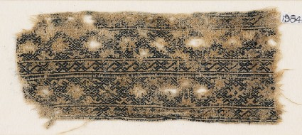 Textile fragment with linked diamond-shapes and interlaced crossesfront