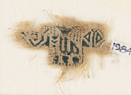 Textile fragment with inscription and an animal, possibly a lionfront