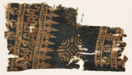 Textile fragment with Arabic-style script, rosettes, and stylized trees or foliagefront