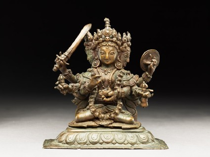 Seated figure of a multi-headed and multi-armed crowned female deityside