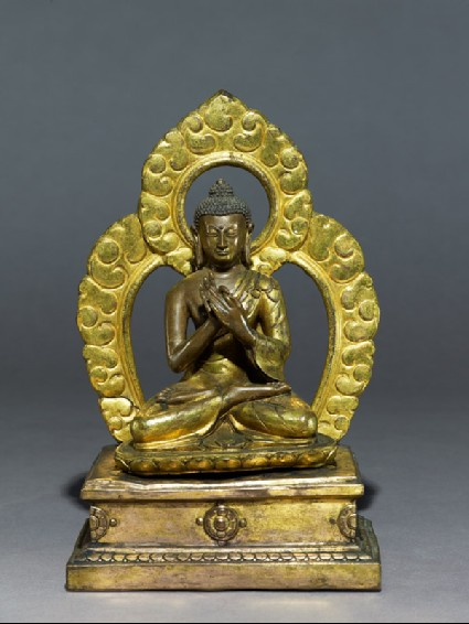 Seated figure of the Buddha with a mandalaside