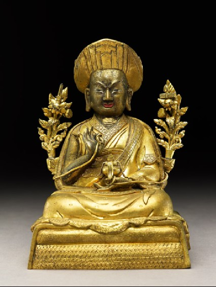 Seated figure of a monk with two flowers, a sword, and scripturesfront
