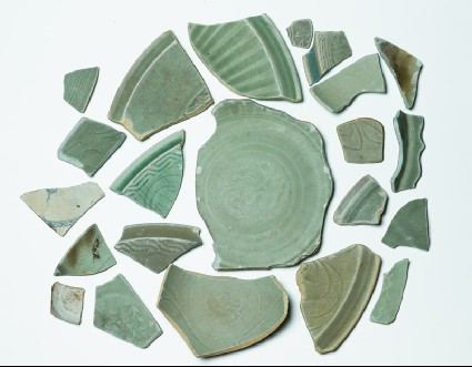 Group of greenware sherds with one blue and white fragmentfront