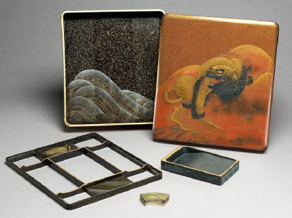 Writing box depicting a tiger on the lid, with a dragon and wave pattern insideoblique, open with contents