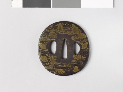 Tsuba with seashells amid waterfront