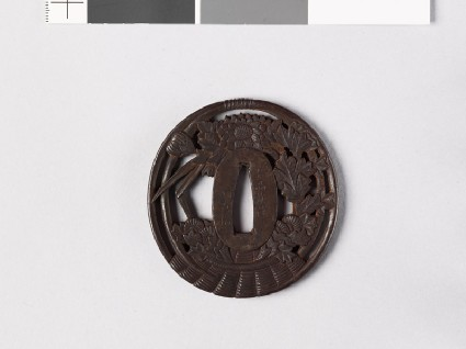 Tsuba in the form of a basket containing iris leaves and chrysanthemumsfront
