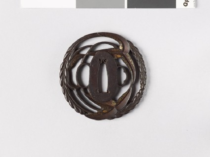 Round tsuba with arrowhead and Cissus leaves, and karakusa, or scrolling plant patternfront