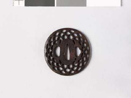 Lenticular tsuba with diaper of overlapping chrysanthemum flowers and leavesfront