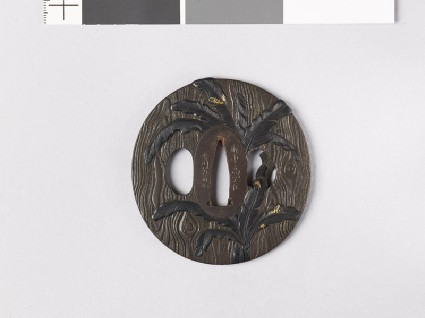 Lenticular tsuba with wood grain decoration and banana treesfront