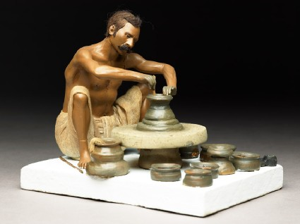 Model depicting a potter turning a pot on a wheelside