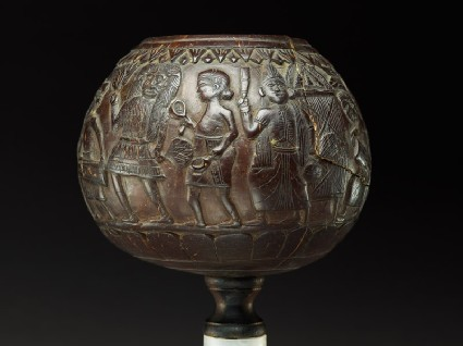 Coconut bowl on stand with procession of figuresside