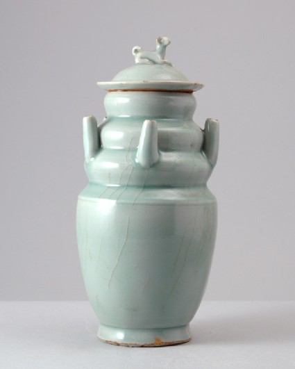 Greenware or qingbai ware funerary vase with lid surmounted by a dogfront